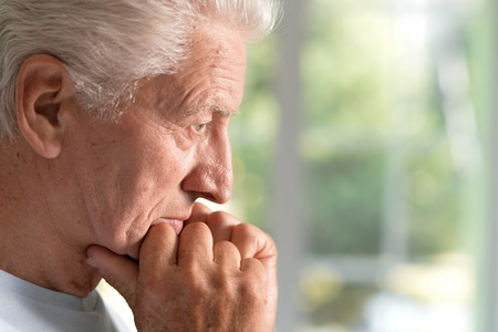 sad handsome elderly man in the room