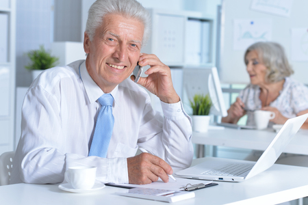 Mature man and woman working together in the office