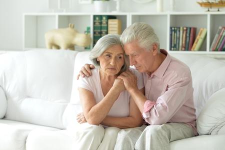 Sad nice elderly couple together at home Standard-Bild