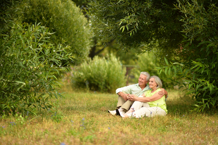 beautiful old people are sitting on the grass in the park Standard-Bild