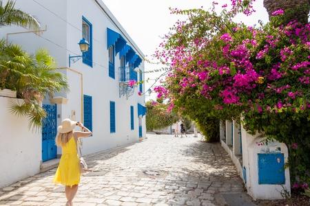 SIDI BOU SAID, TUNISIA - JULY 19, 2018: A woman in yellow dress walking in a city street in Sidi Bou Said, Tunisia, Africa Editorial