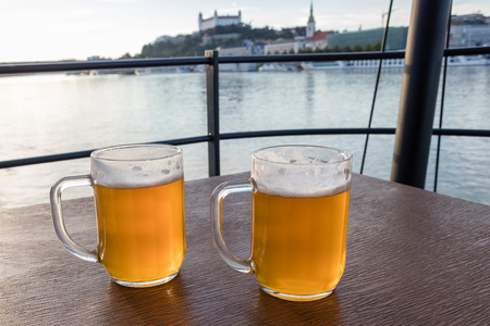 Jugs of beer placed on a wooden table on background river Danube and Bratislava castle, Slovakia