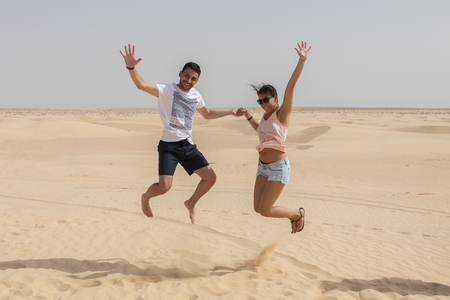 Couple jumping In the air in Sahara Desert, Tunisia, Africa