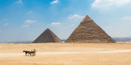 Horse carriage with tourists in front of the Great Pyramids of Giza, Egypt