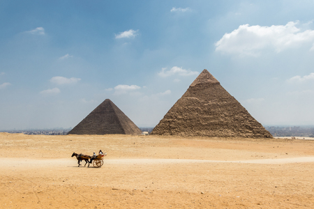 Horse carriage with tourists in front of the Pyramid of Khufu and the Pyramid of Khafre in Egypt