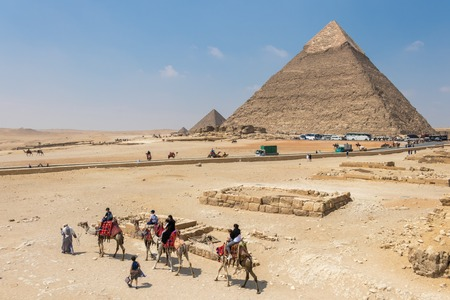 Giza, Egypt - April 19, 2019: Tourists ride on camels guided by a local man at Giza in front of Pyramids, Egypt