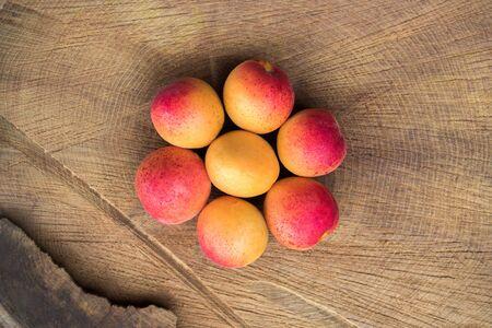 Aprikosenfrucht. Frische Aprikosen auf einem hölzernen Hintergrund. Flache Laienfotografie aus nächster Nähe Standard-Bild