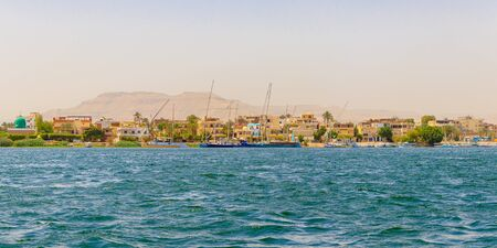 Luxor, Egypt - April 16, 2019: Residential buildings on the Nile river with sailboats in Luxor, Egypt