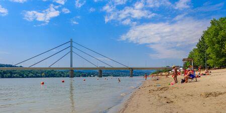 People enjoy on a beach (Strand) on a Danube river, view at Liberty Bridge (Most Slobode) in Novi Sad, Serbia