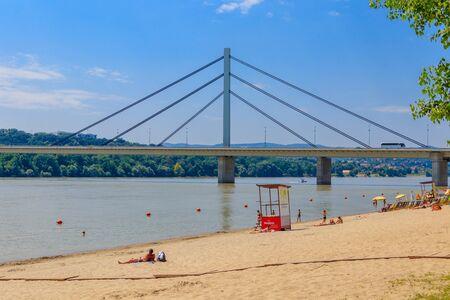 People enjoy on a beach on a Danube river, view at Liberty Bridge in Novi Sad, Serbia 스톡 콘텐츠