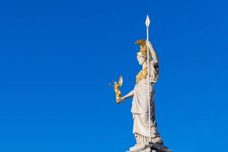 Statue of Pallas Athena Brunnen with blue sky near Parliament building in Vienna, Austria