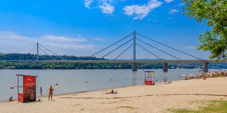 Novi Sad, Serbia - July 3, 2019: People enjoy on a beach (Strand) on a Danube river, view at Liberty Bridge (Most Slobode) in Novi Sad, Serbia