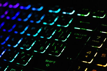 Colorful modern keyboard with rainbow backlight on black background. Backlight of the keyboard in different colors