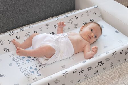 Happy baby girl lying on diaper changing pad, wearing a diaper. Cute adorable baby is 3 months old. Dry and healthy body and skin for children concept. Nursery for children.