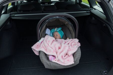 Baby girl sleeping in a safety child car seat.