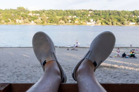 Legs in shoes on holiday, with a view of Danube river in Novi Sad Standard-Bild