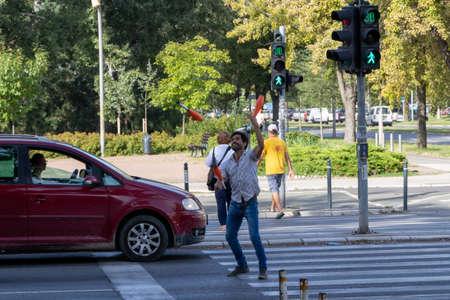 Novi Sad, Serbia - August 31, 2020: A man juggling at a pedestrian crossing in Novi Sad