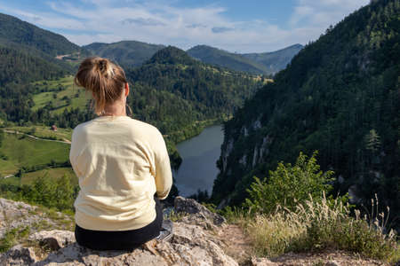 Young girl in the nature. Back view portrait of a single woman watching the Spajici lake from the height in west Serbia