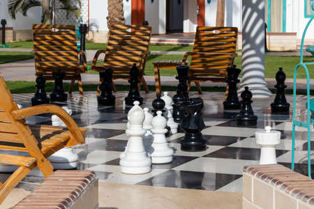 Outdoor giant chess board with the big plastic pieces in the park. 版權商用圖片