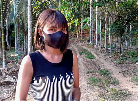 Ranong/ Thailand- 4.1.2020: there is no chance of corona or covid-19, for asian tanned beautiful women, is serious, wears a black mask, in a black-white dress, standing among nature in a rural area. Editorial