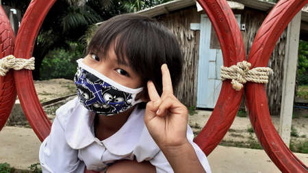 Ranong/ Thailand- 3.31.2020: Asian girl wearing uniform with put up fingers in mask, for prevent spread violence, sitting on black wheels swinging around playing field, the school area, vintage image.