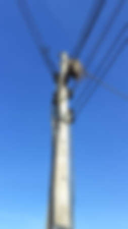 A blackbird, a wild animal, builds nests on the wires, of high voltage poles in rural roads in Thailand on a blue sky and cloudy day in May, blurred texture for background concept.