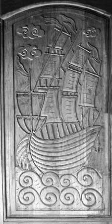 Wood carving boat pattern on black and white background, wooden door, with fish texture carving, vintage decoration.