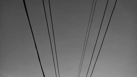 Black and white sky in countryside of Thailand, with selected focus sky image. There are electrical wire captured on vintage sky background. Technology. Place for your text concept.