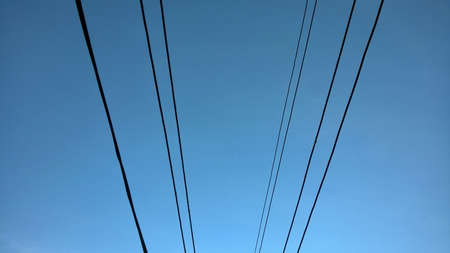 Blue Sky in countryside of Thailand, with selected focus sky image. There are electrical wire captured on blue sky background. Technology. Place for your text concept.