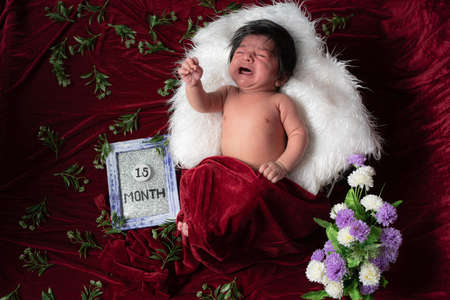 1.5 month baby boy crying while photo shoot rest on while pillow and covering with red velvet shawl