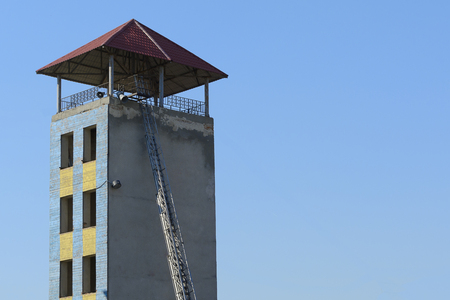 Training fire tower with attached folding ladder for trainings of firefighters.