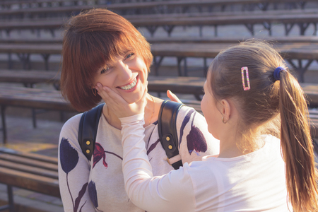 tells: Girl daughter tells mom to smile. The sun is shining at sunset. Mom is smiling. Daughter corrects moms smile. Stock Photo