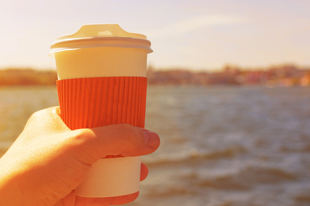 Coffee cup in hand against the backdrop of the lake at sunset.