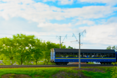 Railway transportation of cars. Tilt shift. Green trees in the background. Stock Photo