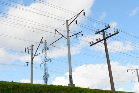 power cables: Supports the electric line of the train, supports the low and high voltage power lines. Against a blue sky background with clouds. Stock Photo