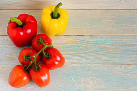 finocchio: Yellow and red peppers and tomatoes on a green branch on a light wooden background