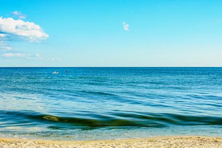 lifevest: Two men kayaking on the horizon of the sea.