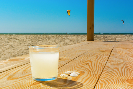 kiteboarding: A glass of soda lemon water on the wooden boards on the beach.