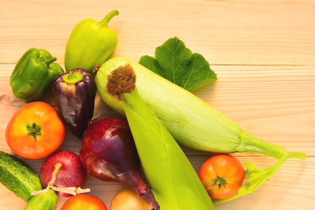 Green, purple peppers, tomatoes, corn, zucchini, blue and yellow onion on a wooden background in diffused light