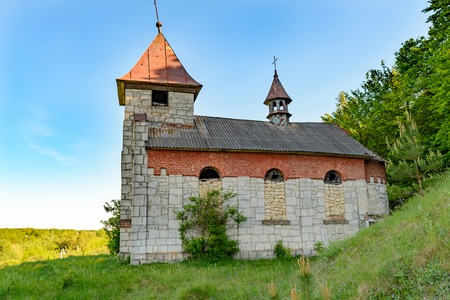 RENIV, TERNOPIL REGION, UKRAINE 12 MAY 2018: An old Catholic church that is not used and is abandoned to the backgrounds of a blue sunny sky with clouds. It was used as a storage facility for chemical