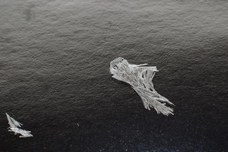 Crystals of salicylic acid on a black background. Small focusing depth.