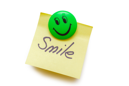 Yellow paper for notes with the words smile on a magnet isolated on white