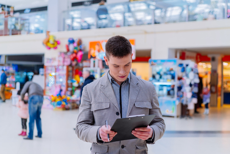 25 30 years: Young man uses tablet in shop.