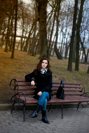 purple shoes: Beautiful Fashion Woman dressed white top, jeans and purple shoes with black handbag sitting and waiting on a bench in the park.