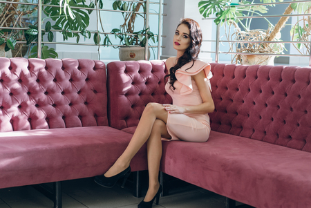 Beautiful young fashionable woman posing in pink dress, smiling, looking at camera. Vogue Style