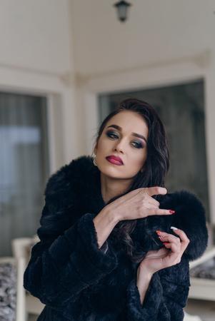 Beautiful girl model in a black coat posing for the camera