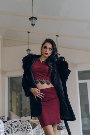 Portrait of fashion model in black coat dress with sunglasses posing in the studio Reklamní fotografie