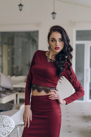 Portrait of a beautiful young brunette woman in red dress