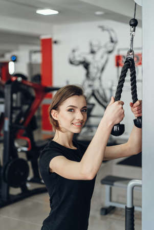 triceps: The girl in the gym performing exercise on triceps Stock Photo