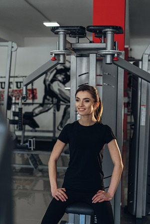 simulators: Beautiful girl in the gym posing for camera near simulators Stock Photo
